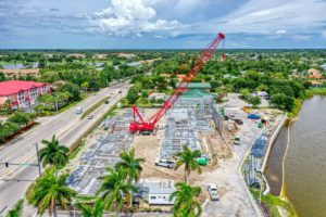 Aerial Drone photography of a construction site in Naples, FL showing a red crane in the middle ground with the beginning of construction of a building